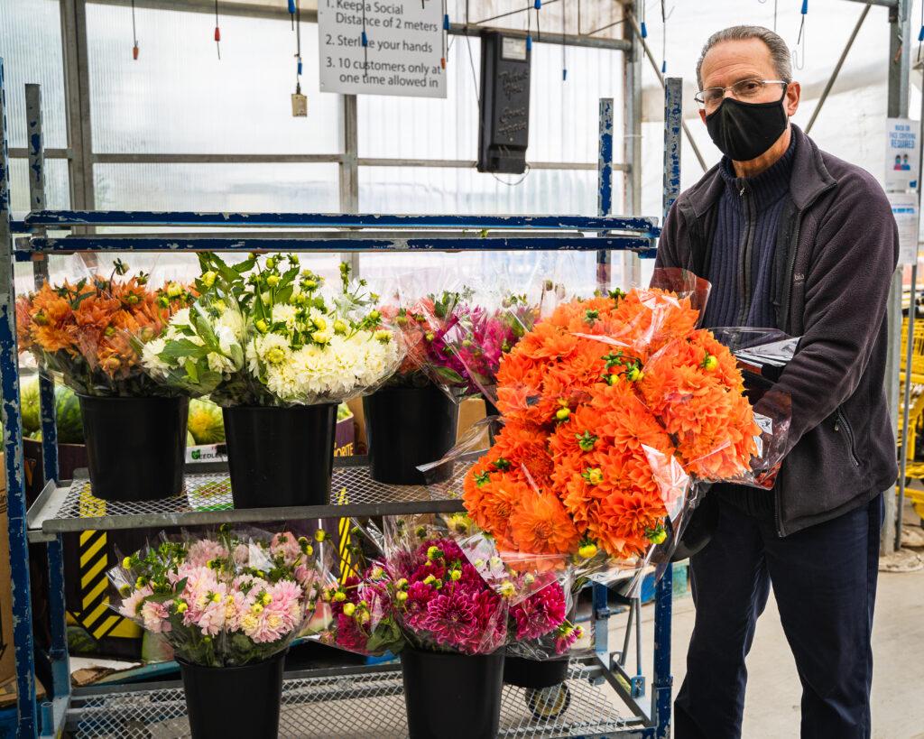 florist holding flowers on display at farmers market