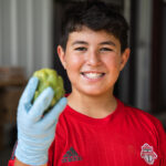 adolescent holding artichoke